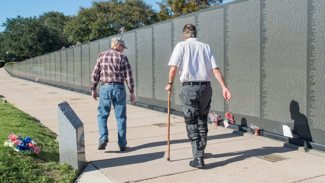 Vietnam War veterans Art Giberson, left, and  Lenny Collins walk along Wall South at Veterans Memorial Park in Pensacola on Tuesday, October 24, 2017.  A plaque, which recognizes these men and others who helped make the park and  Wall South a reality, will be unveiled during a ceremony commemorating its 25th anniversary this year on Veterans Day.