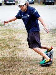"""Justyn Thompson, co-owner of Southern Raft Supply in Woodfin, rides a OneWheel June 23. """"It's really fast, almost that snowboard feeling of carving back and forth,"""" said Thompson of the new electric skateboard."""