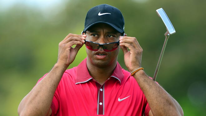 Tiger Woods puts on his sunglasses on the 3rd hole green during the final round of the WGC - Cadillac Championship golf tournament at TPC Blue Monster at Trump National Doral on March 9, 2014.