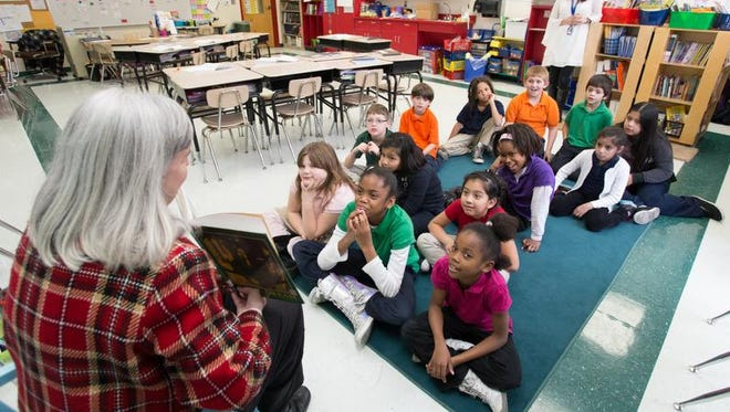 Melissa Spradlin, left, reads a book to a third-grade class at Cockrill Elementary School in Nashville in this 2013 file photo.