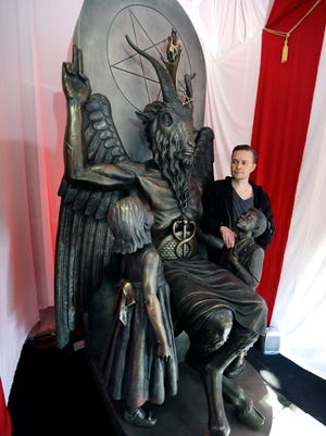 In this Oct. 24, 2016 photo, Lucien Greaves stands next to a 9-foot statue of the goat-headed idol Baphomet at the recently opened international headquarters of the Satanic Temple in Salem, Mass.