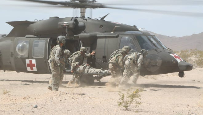 Simulated casualties get loaded onto a helicopter at the National Training Center.