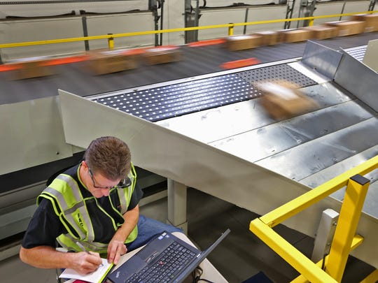Eddie O'Dell monitors the flow of the high speed sorter, as packages zoom by on the sorter's conveyer belt, at Amazon's Whitestown fulfillment center in a December 2014 file photo.