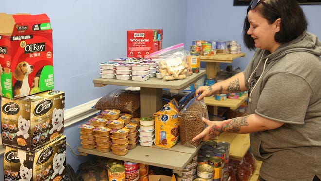 Sylvia Kasch places some donated and much needed dry food on a shelf in the lobby of Jaded Paws Rescue's pet pantry in Jacksonville.