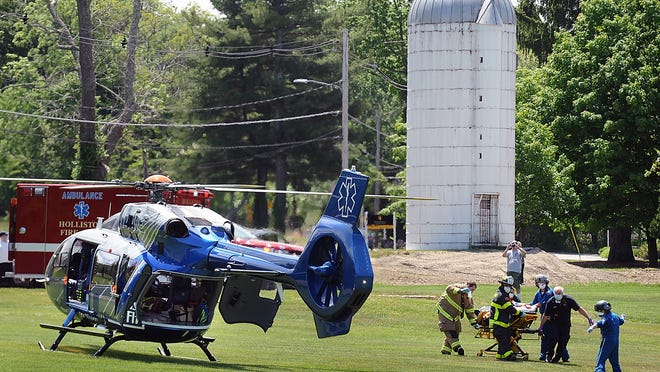 Firefighters and emergency workers bring a Holliston shooting victim to a waiting Boston Med Flight helicopter Tuesday at the Warren Center in Ashland.
