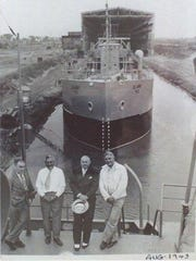 John Odenbach, second from left, stands aboard a ship with others, with the ship canal where finished boats could exit into Lake Ontario behind them.