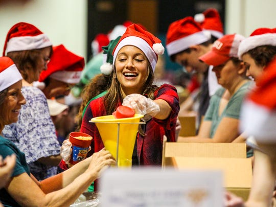 Nicole Basinait, from Fort Myers but home for the holidays from Atlanta, helps her family fill food bags. Holidays Without Hunger, an annual food-packaging event hosted by Meals of Hope,  aimed to package over 700,000 meals in two hours. From 9am to 11am on December 24th, 2016, volunteers from across Southwest Florida gathered at Harborside Event Center in Fort Myers to take action against hunger. A ten-person station is sponsored by local groups, organizations, corporations, and families in order to cover the cost of the meals. All this food packaged on this day stays locally.