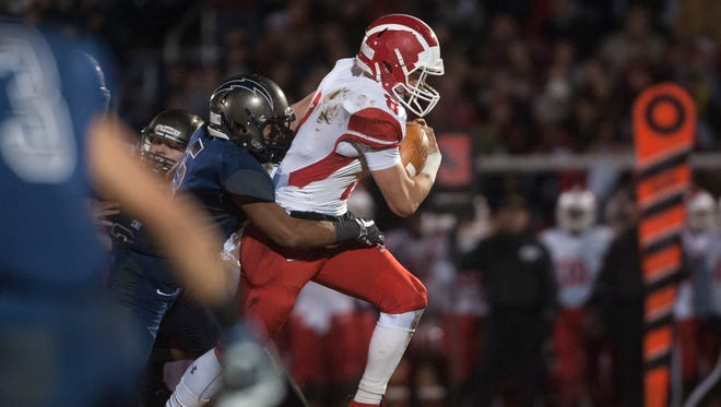 Delsea's quarterback Mason Maxwell is stopped by Timber Creek's Tariq Snead as Maxwell runs the ball  during the first quarter of Friday night's South Jersey Group 3 football semifinal played at Timber Creek High School