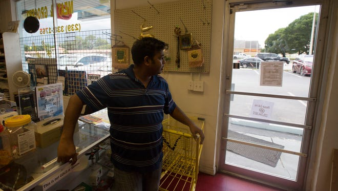 MD Rahman, the owner of the Halal Meat Market and Grocery on Cleveland Avenue, looks out the glass door that he says was broken by a man threatening him and his family if he doesn't close his business. He is one of two Fort Myers Muslim business owners who say they have been targeted by the same man.