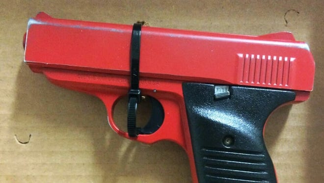 This handgun was painted red to resemble a toy gun.