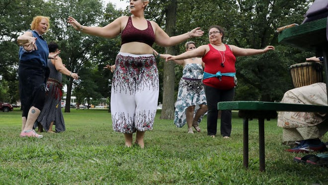 """Jessica Klockau, also known as Elf, of Rock Island, center, leads the """"Bonfire Boogie Class"""" in dancing around a bonfire during drum circles Aug. 17, 2019, at the sixth annual Southeast Iowa Pagan Fest at Dankwardt Park. The seventh annual event will be from 10 a.m. to 5 p.m. Saturday in Dankwardt Park."""