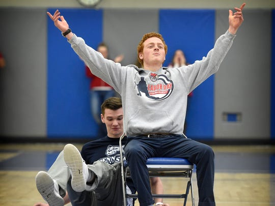 Cedar Crest ice hockey player Reed Hoffman celebrates his victory over basketball player Cody Whitman after playing musical chairs during a King of Hearts pep rally Friday at the school. Twelve Cedar Crest senior boys raised $42,158.85 for the American Heart Association in the King of Hearts competition.