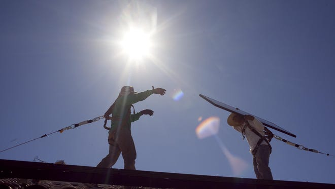 SolarCity employees install a solar panel on the roof of a north Phoenix home in 2010.