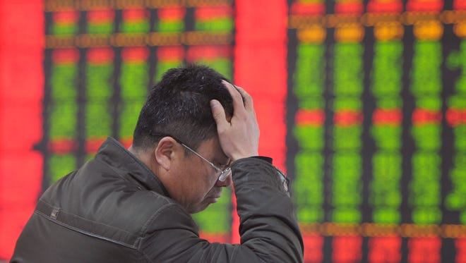 An investor monitors stock prices at a brokerage house in Fuyang in central China's Anhui province Monday, Jan. 19, 2015.