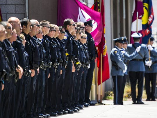 Police officers wait as the body of fallen police officer