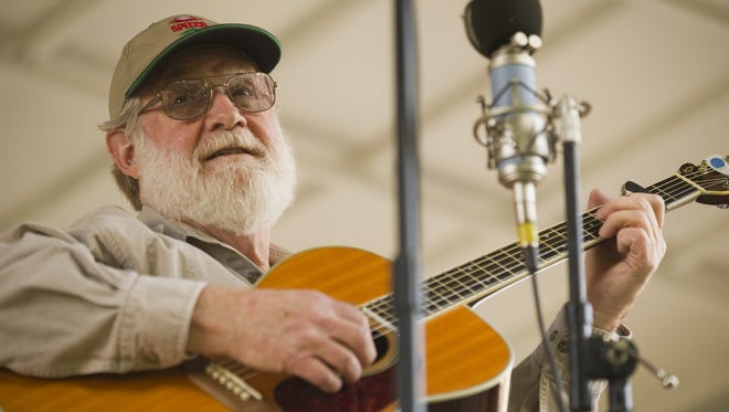 Simon Stanfield of Indianola entertains the Bluegrass Tuesday crowd with old-time folk and blues songs and stories at the Warren County Courthouse lawn.
