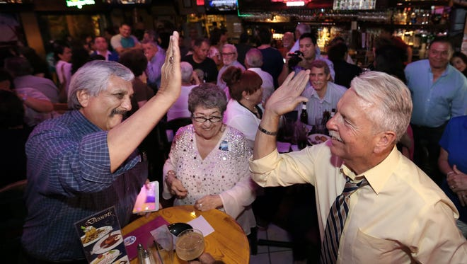 Ricardo Samaniego, right, high-fives his Jefferson High School classmate Raul Lopez after early voting results showed him leading former El Paso Mayor John Cook in the runoff for El Paso county judge. Samaniego won.
