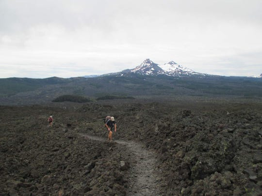 Hikers make their way toward Little Belknap Crater, with North and Middle Sister in the background.