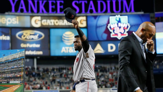 Boston Red Sox designated hitter David Ortiz waves his cap to the crowd as retired New York Yankees pitcher Mariano Rivera walks away, right, after Ortiz was honored before a baseball game between the Yankees and the Red Sox in New York, Thursday, Sept. 29, 2016. (AP Photo/Kathy Willens) ORG XMIT: NYY101