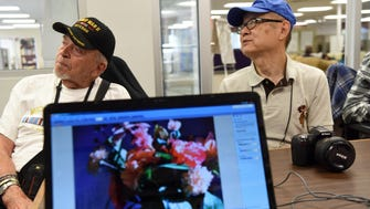 Walter Nolting, 92 and Jerry Liao look at the screen while volunteer teacher Bruce Kalter crops Liao's photograph, displayed on the laptop in the foreground, during a digital photography at the Adler Apashia Center. The class meets once a week to review and critique photographs, crop pictures and use photoshop to enhance pictures.