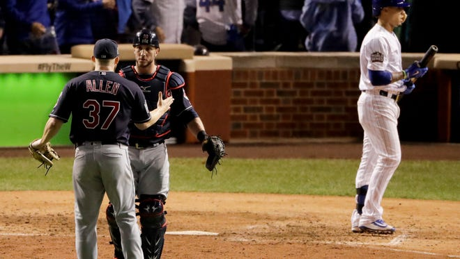 Cleveland Indians catcher Yan Gomes, center, celebrates with relief pitcher Cody Allen after Chicago Cubs' Javier Baez made the final out in Game 3 of the World Series Friday, Oct. 28, 2016, in Chicago. The Indians won 1-0 to take a 2-1 lead in the series.