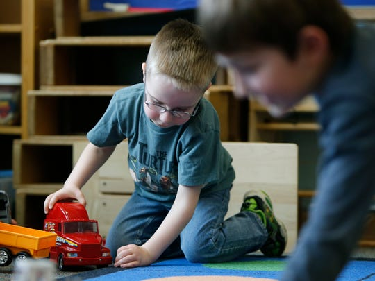 Milo Fosberry plays with a toy truck during kindergarten