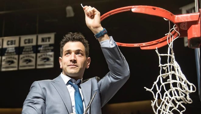 Nevada assistant coach Yanni Hufnagel cuts down a piece of the net at Lawlor Events Center after the Wolf Pack won the Mountain West regular-season championship. Hufnagel and Nevada have mutually parted ways.