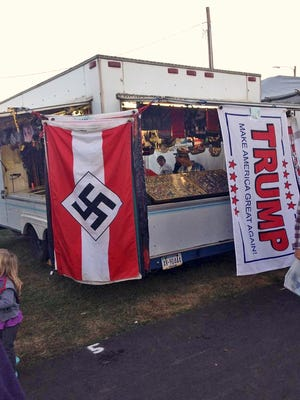 This photo provided by Edward Conner shows a Nazi flag displayed for purchase on a merchandise vendor's trailer Saturday, Sept. 24, 2016, at the Bloomsburg Fair fairgrounds in Bloomsburg, Pa. Bloomsburg Fair organizers shuttered the booth of Lawrence Betsinger, a vendor selling Nazi flags, on Monday, Sept. 26, 2016, after deeming some of his merchandise offensive. Betsinger pleaded guilty to child pornography charges in 2007.
