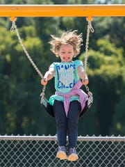 Gianna Buell, a second-grader at Georgetown Elementary School, swings on the new swing set which is part of their new adaptive playground. The new playground equipment can accommodate all students, including those with disabilities.