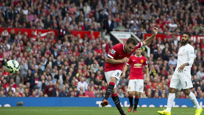 Manchester United's Juan Mata scores against Queens Park Rangers during their English Premier League soccer match at Old Trafford Stadium, Manchester, England, Sunday Sept. 14, 2014. (AP Photo/Jon Super)
