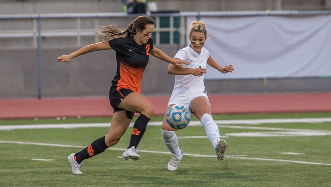 Farmington's Arin Coleman, right, and Aztec's Julianna Mitchell fight for possession on Tuesday at Hutchison Stadium.