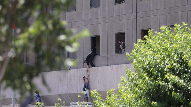 Iranian policemen try to help some civilians fleeing from the parliament building during an attack in Tehran, Iran, on Wednesday.
