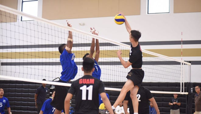 Guam's Giovanni Manglona, right, slams one through the block at an exhibition U19 tournament with three of Guam's youth teams hosting Palau's U19 team at Tiyan High School on Aug. 3.