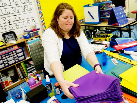 Kindergarten teacher Kasey Powers cleans and organizes