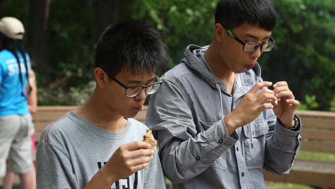 Zhang Le Tao, left, and Wu Siyuan eat s'mores at the Marshfield School Forest near Lindsey on Friday, July 24.