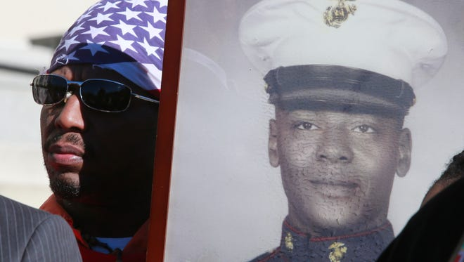 Eddie Garcia of White Plains holds a photo of Kenneth Chamberlain Sr., a man who was shot and killed by the White Plains Police Department,  at a press conference in front of the White Plains Federal Court House on Nov. 11, 2016. Chamberlain was a former United States Marine and retired corrections officer who suffered from mental illness.