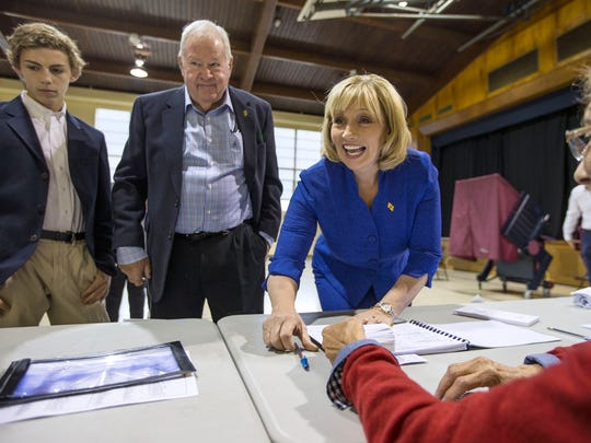 New Jersey Lt. Gov. Kim Guadagno casts her vote on election day at the Parish Center in Monmouth Beach. At left is Guadagno's son Anderson and husband Michael. 