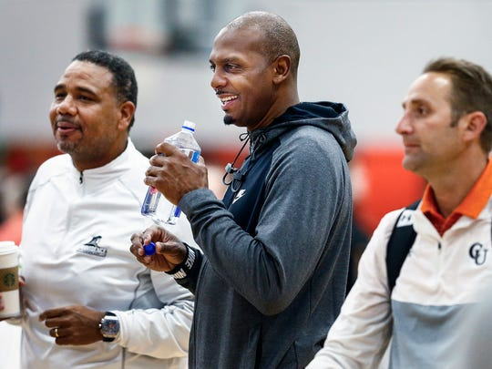 University of Memphis new head coach Penny Hardaway (middle) jokes with Providence head coach Ed Cooley (left) while scouting players on the Bluff City Legends team during Nike EYBL games in Irving, Texas, on April 20, 2018.