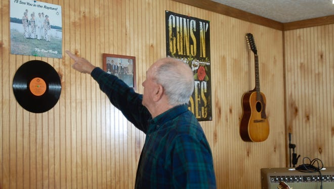 """Tommy Reed points to The Reed Family's second album """"I'll See You in the Rapture!"""" in his music studio on Nov. 2 in Chincoteague, Va."""