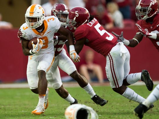 Tennessee running back Ty Chandler (3) escapes a tackle by  Alabama defensive back Shyheim Carter (5) and Alabama defensive back Xavier McKinney (25) during Tennessee's game against Alabama at Bryant Denny Stadium in Tuscaloosa on Saturday, Oct. 21, 2017.