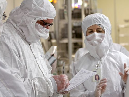 Workers in IBM Burlington's fab must wear protective suits at all times to guard against contaminating microchips during the production process.