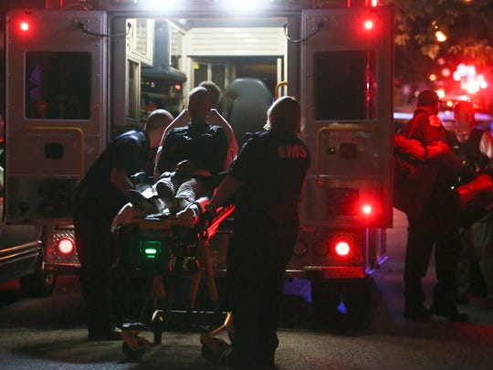 A young person is placed in an ambulance after multiple people were shot in the Hedgeville neighborhood of Wilmington on Tuesday, June 14, 2016.