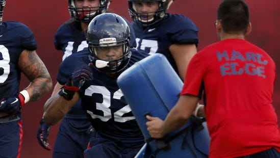 """Linebacker DeAndre' Miller, rushing a dummy during drillls, is """"bigger and stronger"""" than at this time last year."""