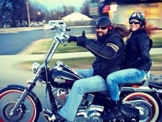 Brian Raymond and Jessica Kelly ride a motorcycle.