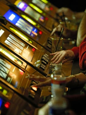 A row of slot machines with gamblers in 2004 at the Agua Caliente Band of Cahuilla Indian's Spa Resort Casino in Palm Springs, Calif.