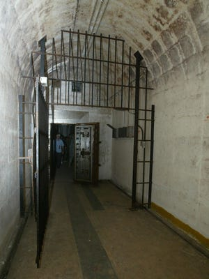 A gate stands open near the end of one of the bunkers at the Birdcage. Just beyond the gate is a safe-like door that leads to the rooms where highly classified weapons were stored.