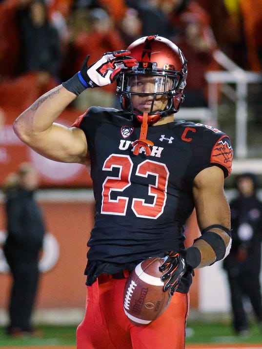 Utah running back Devontae Booker salutes after scoring against Arizona State during the second half of an NCAA college football game Saturday, Oct. 17, 2015, in Salt Lake City. Utah won 34-18. (AP Photo/Rick Bowmer)