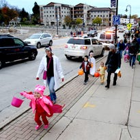 Children and their families skitter along Main Street as they travel store to store for treats before the Menomonee Falls Spooky Walk in Lime Kiln Park on Oct. 27.