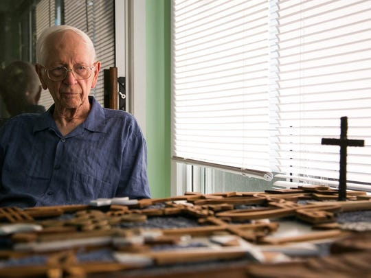With a move to a smaller home Cork Smalley has to find a way to pair down his collection of hand cared wooden crosses. Here he poses for a portrait in his Des Moines home on Wednesday, June 10, 2015.