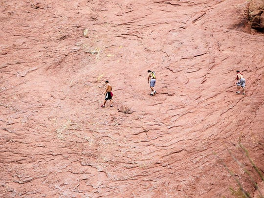 Three hikers stray from the trail during a hike on Echo Canyon Trail on Wednesday evening, July 29, 2015.